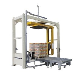 Rotating arm tray wrapping machine
